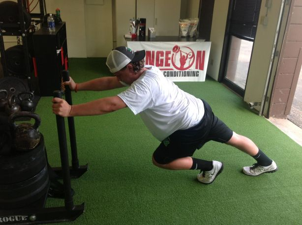 One of our athletes dominating some heavy sled pushes (and showing off the front desk and turf in the process)