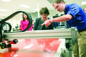 Anne Holton, wife of Democratic vice presidential candidate, Sen. Tim Kaine, D-Va., is shown a 3D printer by Virginia Western student and lab technician London Reinhard on Friday, Sept. 2, 2016 in Webber Hall in Roanoke, Va. Holton toured the community college while campaigning for Hillary Clinton and Tim Kaine, talking about the costs of community college and making it affordable for all Americans. (Heather Rousseau/The Roanoke Times via AP)