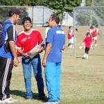 George Navarro (center), President of the Premier Soccer School & Soccer League, converses with other coaches, while one of the Premier teams warm up prior to the first game of the soccer tournament at the Holton Career and Resource Center on Sept. 15.