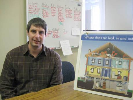 Tom Higgins, energy education director displays a visual aid used in Clean Energy Durham's Pete Street workshops. The board demonstrates how air escapes a home and how residents can stop these leaks to save energy and money. Staff photo by Anna Starnes