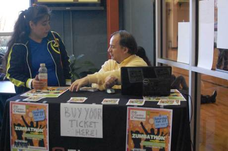 Renee Cunningham, one of the Zumbathon instructors, and Francisco Duque, development and human resources director of El Centro Hispano, sell tickets after Cunningham's Sunday afternoon class at the Downtown Durham YMCA.