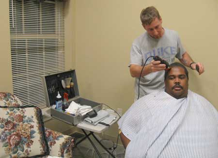 Toby Clayton, 35, gives William Henderson, 27, a haircut at the opening event. (photo: Marissa Peterson)