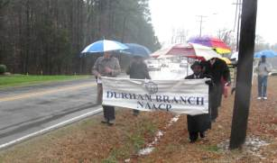 The small group of marchers sing under umbrellas