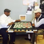 "Bull City Pool Checkers members George Evans(R) and Ernest "" Lash"" Lipson (L) playing a competitive game of pool checkers."