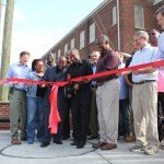 Mayor Bill Bell, surrounded by business owners and community leaders, cut the ribbon in front of the new Angier-Driver streetscape to celebrate the culmination of the 16-month-long project. (Staff photo by Mary Alta Feddeman)