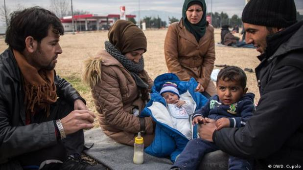 A family sits on a blanket on the ground with a small baby