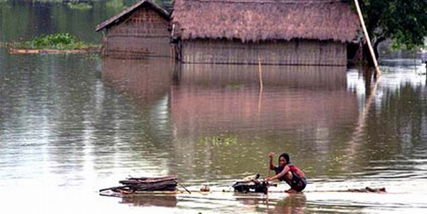 A woman stays adrift on a make shift raft in Assam