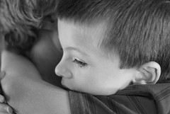 little boy being hugged by an adult