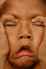 close up of child with hands on face in frustration