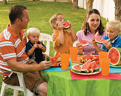 family at table eating watermelon