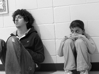 girl sitting next to larger boy looking frightened