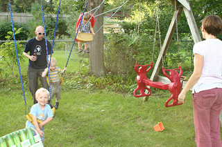kids and parents playing in backyard at swingset
