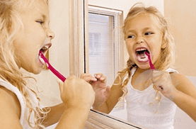 young girl brushing teeth looking in bathroom mirror