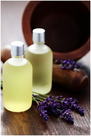 2 bottles of massage oil with lavendar lying nearby