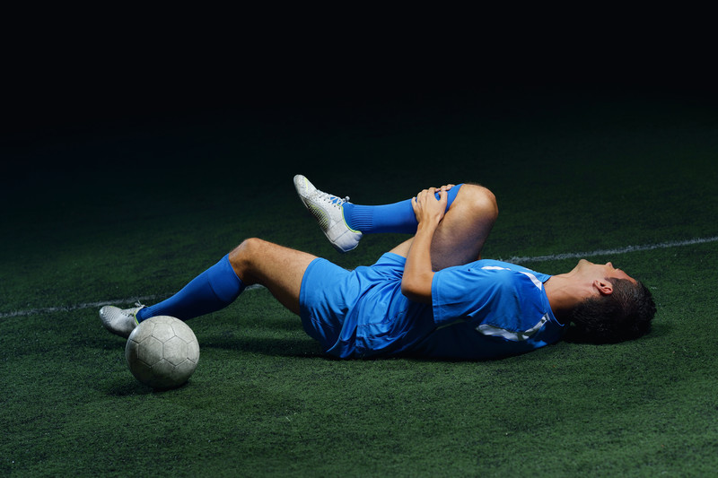 athlete laying on ground stretching