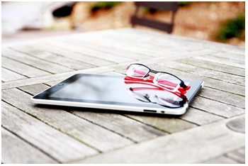 electronic tablet with reading glasses laying on it