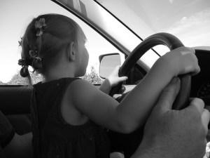 young girl helping parent drive car