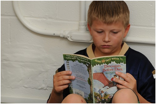 boy reading fiction book while leaning against wall