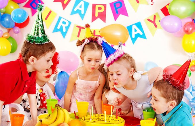 children around cake at birthday party
