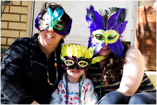 family wearing feathered masks