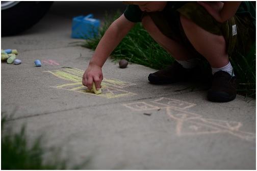 child making art on sidewalk