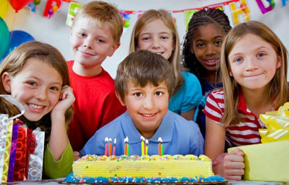 children smiling in front of birthday cake