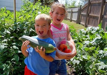 happy boy and girl showing off produce in garden