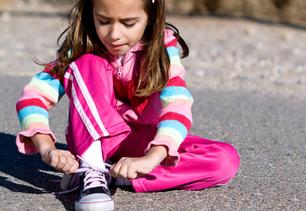 young girl sitting down, tying her shoe