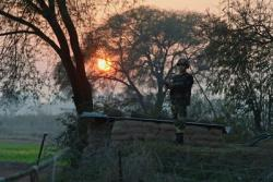An Indian Border Security Force soldier keeps watch at an outpost along the India-Pakistan border in Abdulian 38 kms southwest of Jammu on 9 January 2013 (Photo: AAP).