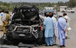 Pakistani security officials inspect the damaged vehicle of Ibrahim Jatoi, an election candidate of National Peoples Party, after a suicide bomb attack, in Shikarpur, Sindh province, Pakistan (Photo: AAP).