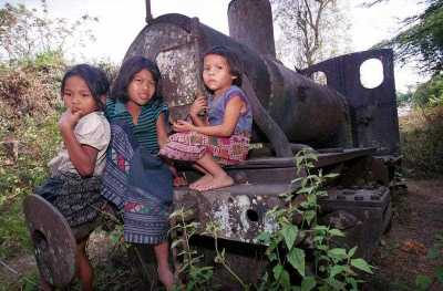 A trio of Laotian children play on a rusting narrow gauge locomotive. (Photo: AAP)