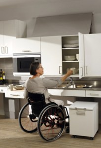 lowered kitchen cabinet accessed by woman in wheelchair
