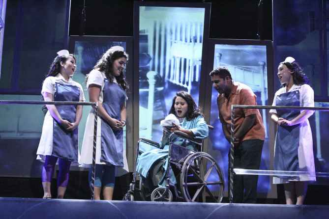"""It's a Boy:"" Mrs. Walker (Deedee Magno Hall) meeting her newborn son, with Uncle Ernie (Parvesh Cheena) and the nurses (L-R Christine de Chavez, Caitlyn Calfas, Tina Nguyen) looking on in in the East West Players production of ""The Who's Tommy"". Photo by Michael Lamont."