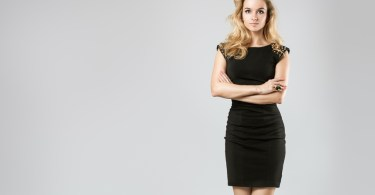Full Length Portrait of a Sexy Blonde Woman in Little Black Dress. Crossed Arms and Legs. Closed Body Posture. Body Language Concept.