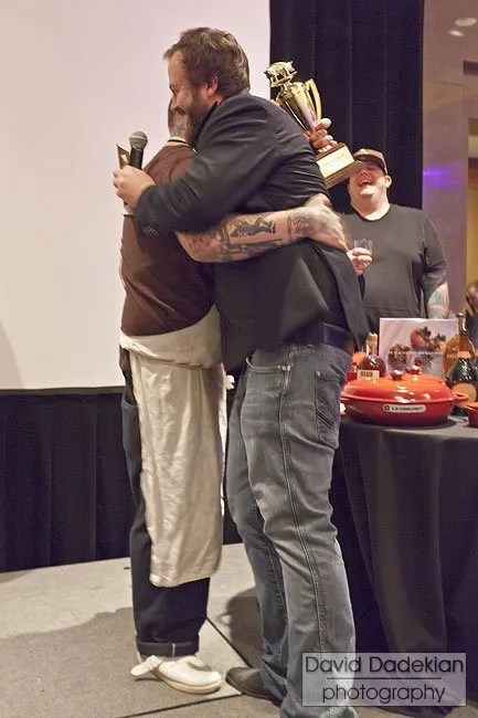 Chef Jamie Bissonnette and Cochon 555 founder Brady Lowe embrace after Lowe announces Bissonnette as the Boston winner. Chef Matt Jennings cheers in the background