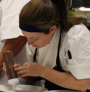 Chef Lucia Bobby concentrates as she prepares the plate for dessert