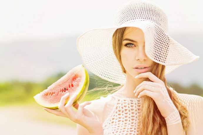 Beautiful young woman with crochet hat and watermelon slice