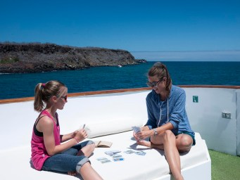 ECUADOR, Galapagos, Anaïs and Ali playing cards on the sundeck of the Letty