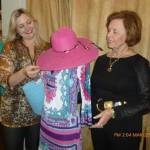 "Caroline Bland, owner of Mercy Me! in Edgefield, shows Dixie Culbreath the fashion show's Model Coordinator, a beautiful spring dress, hat and matching purse selected for this year's ""Southern Belles."""