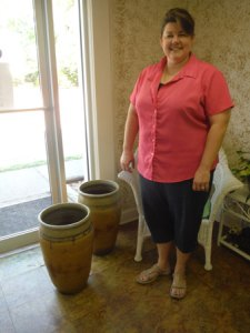 Here the Doggone Potter stands with two of her first pots, in her shop.