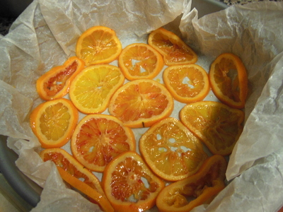 Placing the oranges in the tin, bottom and sides