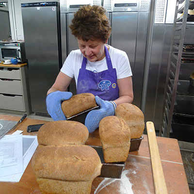 Danielle helps us tease the very well-risen brown loaves out of their tins.