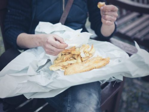A woman eats fish and chips on her lap.