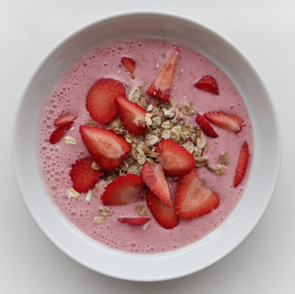 Kefir and strawberry smoothie with cereal and strawberries. Refreshing, sweet and good-for-you summer breakfast.