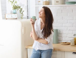 γυναίκα πίνει καφέ στη κουζίνα