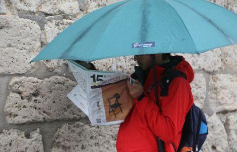 Un hombre se protege de la lluvia con un paraguas mientras lee (Ical)