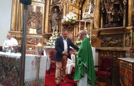 Silvano estrechando la mano de Antolín de Cela tras posar el ramo a los pues de la Patrona