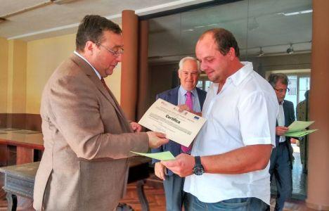 Uno de los alumnos del programa Ancares III recogiendo su diploma de manos del alcalde de Villafranca