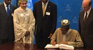 Finally, Mr President puts pen on paper. Environment Minister, Amina Mohammed, and others look on