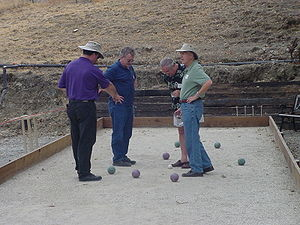 Four bocce players standing around a jack whil...